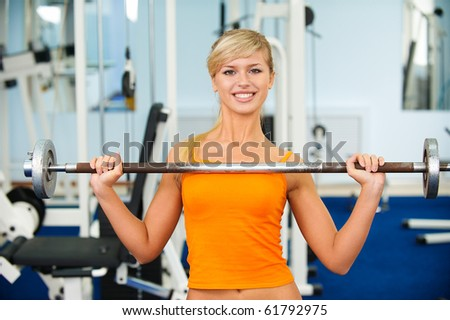 portrait of blonde girl exercising in gym with weight