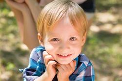 Portrait of blonde little boy posing outside