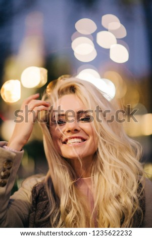 Portrait of blonde on background of evening city #1235622232