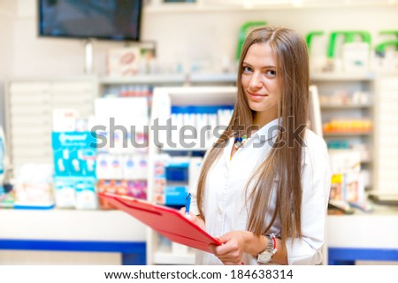 portrait of blonde pharmacist or health care worker with red clipboard in pharmacy
