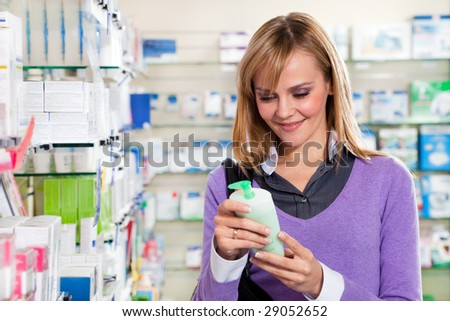 Portrait of blonde woman reading label of shampoo in pharmacy. Copy space