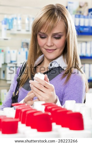 Portrait of blonde woman shopping in pharmacy.