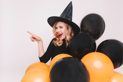 Portrait of blonde woman with surprised smile preparing for halloween party. Indoor photo of curly girl wears black dress and witch hat enjoying themed event.