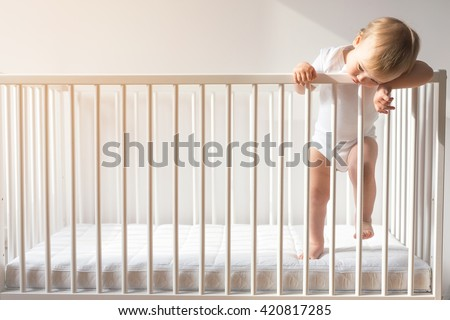 Portrait of bored baby standing in crib. Baby boy stand alone in crib. Sad little baby. Lonely baby stay in the crib. Waif child. Loneliness.