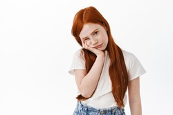 Portrait of bored cute red head little girl with freckles, face palm and stare at something boring, sulking upset, standing bothered against white background