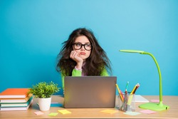 Portrait of bored high school girl sit desk look copyspace wear green shirt isolated over blue color background