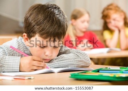 Portrait of bored pupil putting his head on desk and drawing something in copybook at lesson