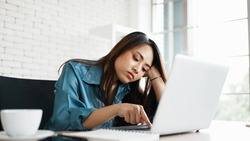 Portrait of bored young asian woman typing laptop in office. Freelance employees sleeping lying head on hand on computer desk feel boring. Lifestyle of routine employees concept.