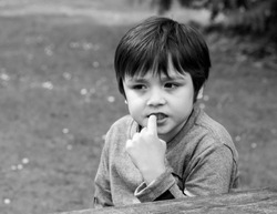 Portrait of boy biting his finger nails while looking at something, Emotional child portrait in black and white, Kid siting alone with thinking face or nervous Child putting finger in his mouth.