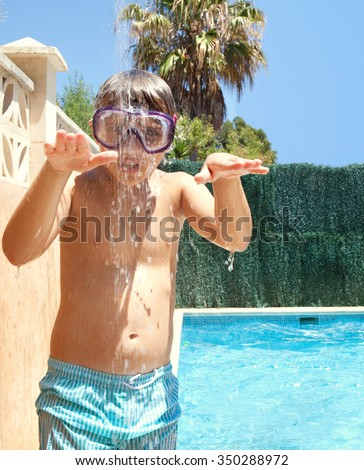Portrait of boy child under a shower having fun in swimming pool home garden on a sunny summer holiday, outdoors. Active kids lifestyle, pulling faces wearing diving mask, house exterior vacation.