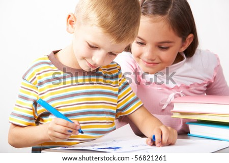 Portrait of boy drawing on the paper with curious girl looking at it near by