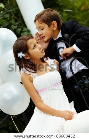 Portrait of boy groom whispering secret to his bride