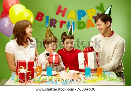 Portrait of boy holding his present with happy parents and brother near by