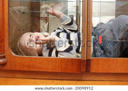 Portrait of boy in cabinet at home