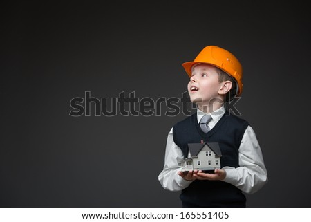 Portrait of boy in hard hat keeping home model on grey background