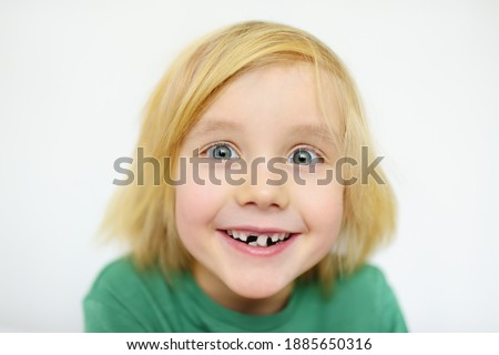 Photo of  Portrait of boy shaking wobbly milk tooth in open mouth before it changes to the molar. Stages of growing up a child. Health care and dental hygiene for baby. Childhood