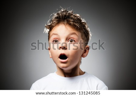 Portrait of boy surprised on gray background