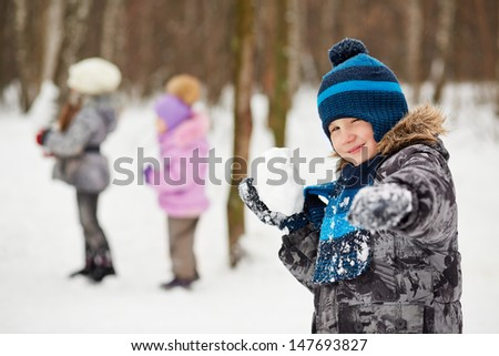 Portrait of boy which aims with snowball screwing up one eye in winter park - stock photo