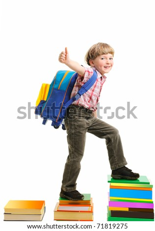 Portrait of boy with backpack walking from top to top of book piles