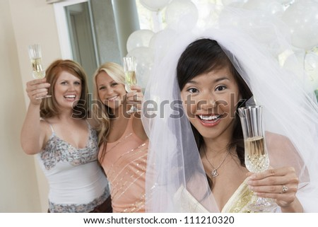Portrait of bride and friends holding champagne flute at party