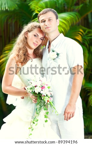 Portrait of bride and groom in a tropical garden.