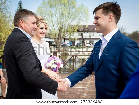 Portrait of brides father shaking hands with groom at wedding ceremony