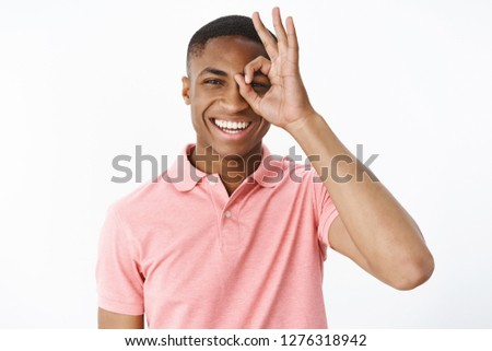 Portrait of bright and cheerful young dark-skinned guy in pink polo shirt showing okay or zero gesture over eye looking through it and smiling broadly enjoying life without problems over gray wall