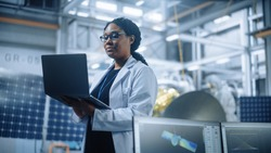 Portrait of Brilliant Female Engineer Confident and Focused Thinking, working at Aerospace Satellite Manufacturing Facility. Top World Scientist Doing Science and Technology Research in Space Program
