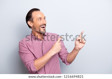 Portrait of bristle brunete hair man with open mouth staring eyes in casual wear point finger aside up on new novelty promotion or decision isolated on light gray background with copy space for text #1216694821