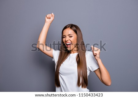 Portrait of brown-haired gorgeous attractive nice excited young lady celebrating victory over grey background, isolated