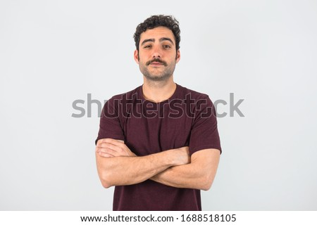 Portrait of brown, smiling, handsome man with mustache and purple t-shirt standing with crossed arms. Gray background. Stock foto ©
