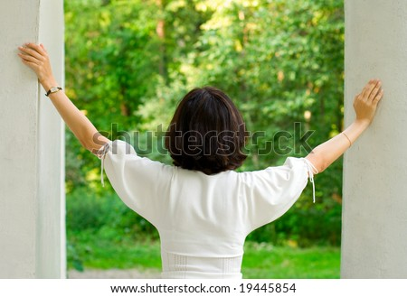 portrait of brunet woman in white dress looking out window of old house