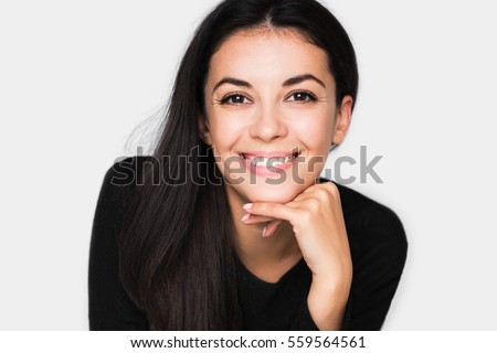 Portrait of brunette cute woman with beautiful and healthy toothy smile, with hand on chin. Young happy pretty woman wearing black sweater on light grey background. Positive and happiness mood.