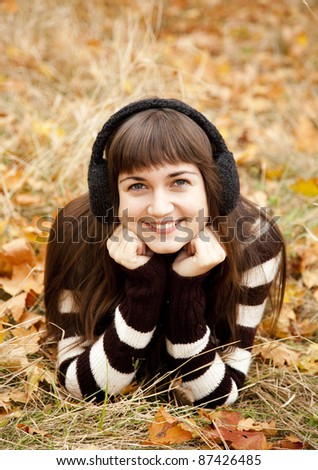 Portrait of brunette girl in the autumn park. Outdoor shot.
