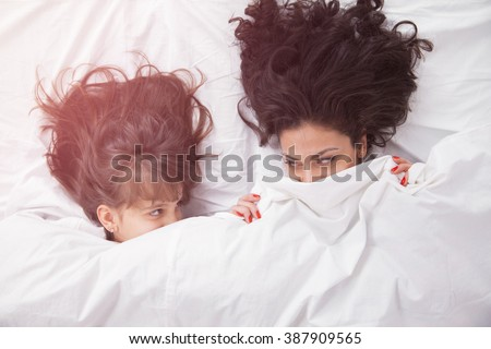 Portrait of brunette long hair mother and daughter under the duvet together in soft morning light on white linen bed. Concept of happy family living, relaxation, comfort, fun. Top view.