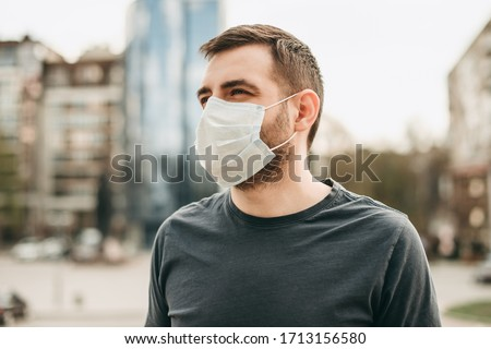 Portrait of brunette man in a medical surgical mask in the summer city. Coronavirus, illness, infection, quarantine.