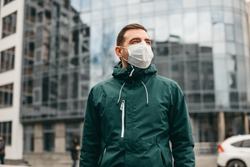 portrait of brunette man in a surgical bandage on a background of a modern building, coronavirus, illness, infection, quarantine, medical mask