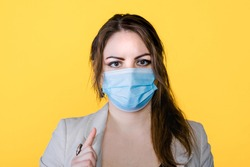 Portrait of brunette woman in face medical mask in studio with yellow isolated background