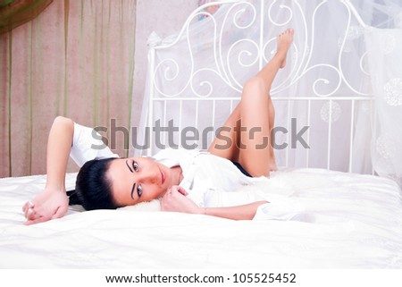 Portrait of brunette woman on the bed with white bed linen.