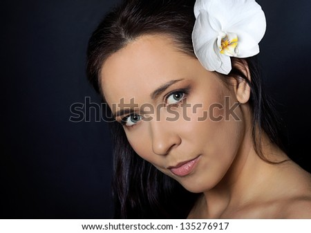 portrait of brunette woman with white orchid over black background