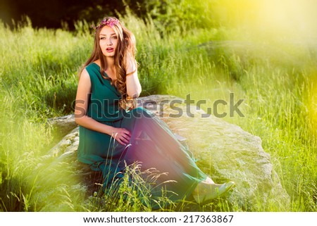 portrait of brunette young beautiful woman sitting on stone in green dress with pink wreath of flowers & sun light flares of rays & looking at camera on summer outdoor copy space background