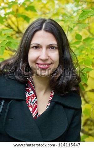 Portrait of brunette young woman on autumn background - stock photo