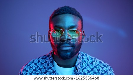 Portrait of brutal Afro American young man wearing trendy tinted yellow lens sunglasses seriously looking straight on camera in pink neon light. Advertising concept. Urban style, fashion, mood