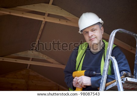 Portrait of builder standing by ladder with hard hat and high visibility jacket