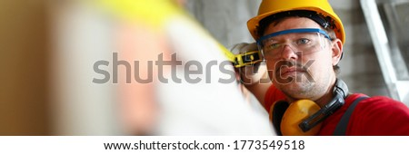 Portrait of builder with measuring tape. Foreman checking quality of work, man with tool for looking at level. handyman with instrument, person wearing protective helmet