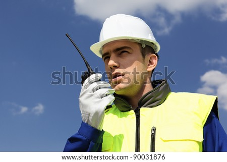 portrait of builder with transmitter in blue sky