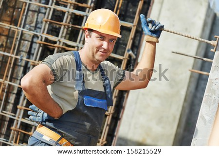 Portrait of builder worker concreter with metal rods bars at framework reinforcement for concrete pouring in construction site #158215529