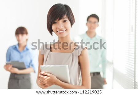 Portrait of business associates with a young female leader in the foreground