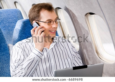 Portrait of business man calling by phone in the airplane