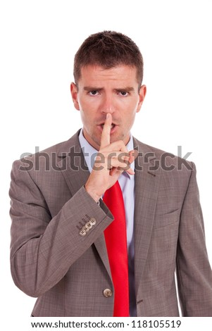 Portrait of business man showing silence gesture with his forefinger by mouth